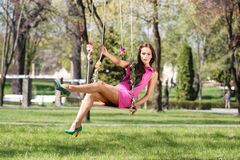 Sexy pink purple dress lady on a swing Royalty Free Stock Images