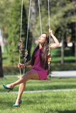 Sexy pink purple dress lady on a swing Royalty Free Stock Photos
