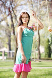 Sexy pink purple green dress lady on a swing Royalty Free Stock Image