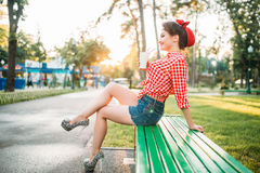Pinup girl holds cardboard cup with a straw. Pinup girl sitting on brench and holds cardboard cup with a straw, city park on background. Vintage american fashion stock photo
