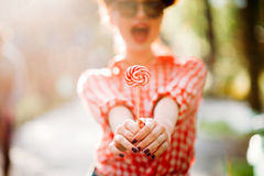 Sexy pinup girl holds out a hands with lollipop Stock Photo