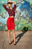 Pinup girl. Hot brunette pinup woman model wearing red headband, checked shirt and skirt, black high heels, posing, standing against green and blue grafitti royalty free stock photos