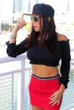 Sexy Playboymodell im Balkon mit roter Sportkleidung und im Hut im Sport beschuht Js Lizenzfreies Stockbild