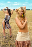 Playful women. Two playful women posing in the field stock image