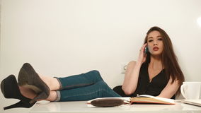 playful young brunette business woman talking by phone in the office background