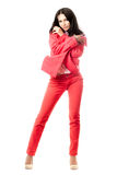 Sexy playful young brunette in red suit. Isolated Stock Image