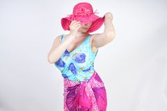 Sexy plus size girl in a blue swimsuit, fuchsia hat with brim and in a trendy bright pareo stands on a white background in the Stu stock image