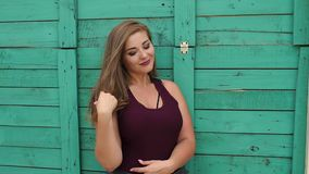 Portrait of a young girl overweight in the Park against the green wall. Girl XXL. Plus size model posing on camera in a Park near a green vintage wooden wall stock video