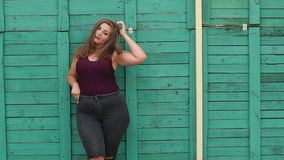 Plus size model posing on camera in a Park near a green vintage wooden wall. Long hair. Slow motion stock video