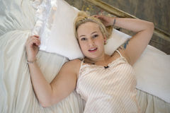 Plus size woman on a bed. Plus size blonde woman lying on her back on a white bed. She is wearing a pink nighty royalty free stock photo