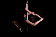 Sexy pole dancer in dark setting. Dramatic portrait of a gorgeous athletic pole dancer holding a pose Stock Images