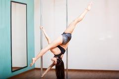Sexy pole dancer doing a leg split Stock Photos