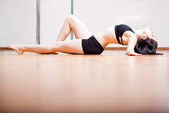 Sexy pole dancing routine. Cute young brunette laying on the floor and arching her back during a pole dancing routine Royalty Free Stock Images