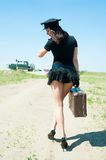 Sexy police woman going with old suitcase Royalty Free Stock Image