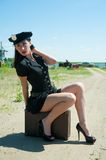 Sexy police woman sitting on old suitcase Royalty Free Stock Photography