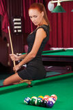 Sexy pool player. Beautiful young female pool player in black dress holding cue and looking at the billiard table Stock Photo