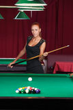 Sexy pool player. Beautiful young female pool player in black dress holding cue and looking at camera Stock Photo