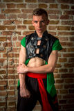 Sexy portrait of a very muscular Caucasian male model dancer in national costume against a brick wall Stock Photo