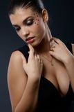 Sexy portrait of woman in fancy makeup. Sexy portrait of woman posing in seductive black dress with cleavage in fancy makeup with strasses Stock Photography