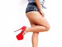 Sexy pose for pretty woman in sexy red shoes. Isolated sexy woman in her early 40s wearing micro denim shorts and high heel shoes Stock Photos