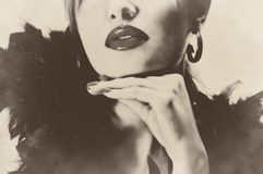 Sexy pretty beautiful woman with black feathers, shiny lips sepia retro vintage Royalty Free Stock Image