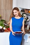 Sexy pretty beautiful woman with white teeth smile wear slim fit. Blue dress in the kitchen eats sweet tasty cake baking makeup diet right food cook chef Stock Photos