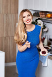 Sexy pretty beautiful woman with white teeth smile wear slim fit. Blue dress in the kitchen eats sweet tasty cake baking makeup diet right food cook chef Stock Image