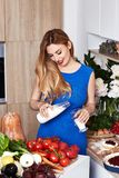Sexy pretty beautiful woman with white teeth smile wear slim fit. Blue dress in the kitchen eats sweet tasty cake baking makeup diet right food cook chef Royalty Free Stock Images