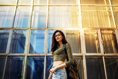 Sexy and pretty brunette in glasses with bag. Sexy and pretty brunette in glasses posing on the streets with backpack Stock Photos