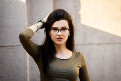 Sexy and pretty brunette in glasses posing on the streets. Royalty Free Stock Images