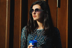 and pretty brunette in sunglasses with coffee in hand Stock Images