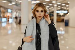 Sexy pretty stylish young blond woman with gray eyes in a luxurious gray coat with a vintage scarf with a fashionable bag stock photography