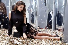 Sexy pretty woman sit floor with lot of golden sequins glamour f. Ashion model bright makeup perfume wear black stylish dress celebration party holiday beauty Royalty Free Stock Photography