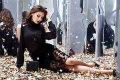 Sexy pretty woman sit floor with lot of golden sequins glamour f. Ashion model bright makeup perfume wear black stylish dress celebration party holiday beauty Stock Photo