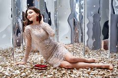 Sexy pretty woman sit floor with lot of golden sequins glamour f. Ashion model bright makeup perfume wear lace stylish dress celebration party holiday beauty Royalty Free Stock Photo