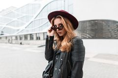 Sexy pretty young hipster woman in sunglasses in vintage hat in trendy leather jacket with black backpack stands