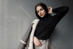 Sexy pretty young woman in an elegant checkered coat with white fur in a black stylish shirt in vintage gray pants poses