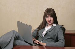 Sexy professional woman on a laptop. Twenties brunette professional typing on a laptop computer Royalty Free Stock Photo