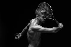 Sexy racket. A portrait of a tanned sportive tennis player with a racket against black background Royalty Free Stock Images