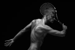 Racket. A portrait of a tanned sportive tennis player with a racket against black background royalty free stock photo