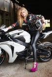 Sexy Radfahrerfrau auf einem Motorrad Stockbilder