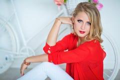 Sexy recht blondes Mädchen mit blauen Augen im roten Hemd Stockbild