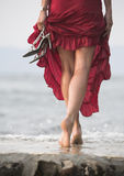 Sexy red dressed woman walks on wet stone next to sea Royalty Free Stock Photo