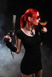 Sexy red hair woman with a gun and a cocktail Stock Photos