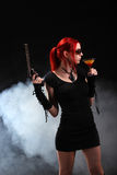 Sexy red hair woman with a gun and a cocktail Royalty Free Stock Image