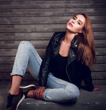 Sexy red hair woman posing in black jacket and blue jeans on str Royalty Free Stock Photos