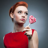 Sexy red-haired girl holding candy Royalty Free Stock Images