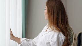 Sexy red-haired girl in a white shirt stands near the big window in the bedroom. A happy young woman in a white shirt is standing near a bright window in the stock video