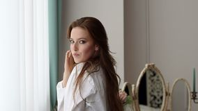 Sexy red-haired girl in a white shirt stands near the big window in the bedroom. stock footage