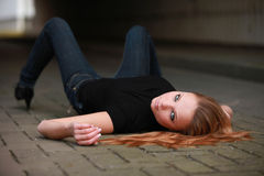 Sexy red haired teenager. Sexy long red haired teenager with jeans and high heels lying on back looking over shoulder Royalty Free Stock Image